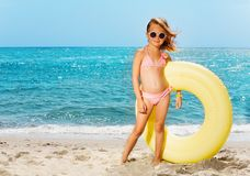 Little girl with big rubber ring on the beach Stock Image