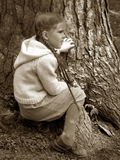 Little Girl - Big Tree. A pretty little girl sitting by a tree.  Sepia tone image Royalty Free Stock Photos