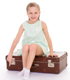 Little girl with a big and very old suitcase. Stock Photo