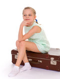 Little girl with a big and very old suitcase. Stock Photos