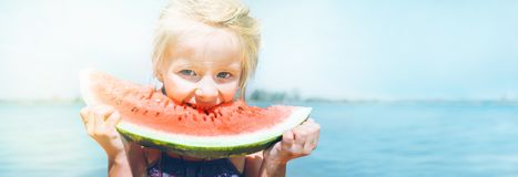 Little girl with big watermelon segment funny portrait. Healthy eating concept image. Little girl in pink sunglasses with big watermelon segment funny portrait stock photography