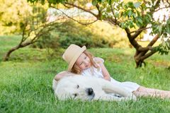 Little girl with a big white dog in the park. A beautiful 5 year old girl in white dress hugs her favorite dog during a summer wal. K stock image