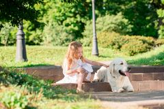 Little girl with a big white dog in the park. A beautiful 5 year old girl in white dress hugs her favorite dog during a summer wal. K stock photos