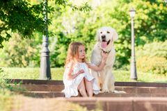 Little girl with a big white dog in the park. A beautiful 5 year old girl in white dress hugs her favorite dog during a summer wal. K royalty free stock image