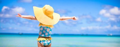 Little girl in big yellow hat on white sandy beach Royalty Free Stock Images