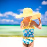Little girl in big yellow hat on white sandy beach Royalty Free Stock Image