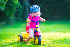 Little girl on a bike. Children riding a bike. Kids enjoying a bicycle ride. Little preschooler girl having fun outdoors. Active toddlers play in the garden Stock Images