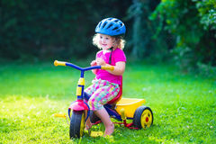 Little girl on a bike. Children riding a bike. Kids enjoying a bicycle ride. Little preschooler girl having fun outdoors. Active toddlers play in the garden Stock Image