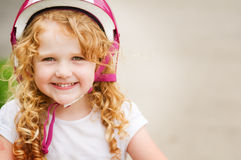 Little girl in a bike helmet. Happy four year old girl wearing a pink bike helmet Royalty Free Stock Photo