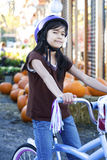 Little girl with bike helmet on bicycle Royalty Free Stock Photography