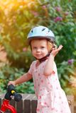 Little girl with a bike. Little girl with bicycle and helmet smiling royalty free stock image