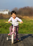 Little girl on a bike near the house Royalty Free Stock Photo