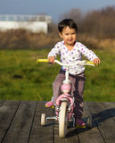 Little girl on a bike near the house Royalty Free Stock Images