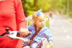 Little girl on bike seat cycling with mother Royalty Free Stock Images