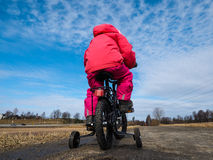 Little girl biker wearing pink on gravel road. With supporting wheels on gravel road at spring with blue sky Stock Image