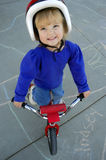 Little Girl Biking. Motion shot of little girl biking with red helmet Royalty Free Stock Photos
