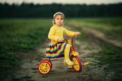 Little girl biking on the road Stock Photos