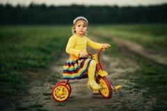 Little girl biking on the road stock photos