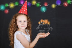 Little girl in birthday hat hold a birthday cake drawing on blac Stock Image