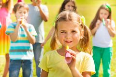 Little girl on birthday. Little 5 years girl on birthday party holding noisemaker horn, smile and having her friends on background Royalty Free Stock Images