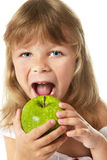 Little girl bites apple Royalty Free Stock Images