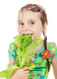 Little girl bites green leaf lettuce Royalty Free Stock Photos