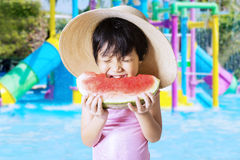 Little girl bites watermelon at pool Royalty Free Stock Images