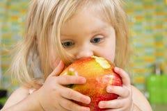 Little girl biting an apple Royalty Free Stock Photo