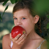 Little girl biting into an apple Royalty Free Stock Image