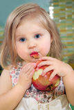 Little girl biting an apple Stock Images