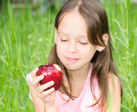 Little girl biting apple Royalty Free Stock Photography