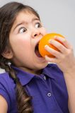 Little girl biting big orange. Royalty Free Stock Photo