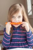 Little girl biting on a carrot Stock Photo