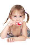 Little girl biting red heart-shaped lollipop Stock Photography