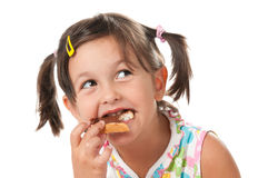 Little girl biting a snack Royalty Free Stock Photos