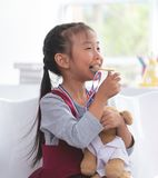 Little girl bitting gold medal for student award stock images