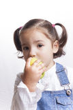 Little girl bitting a green apple Royalty Free Stock Image