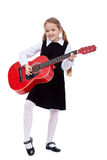 Little girl in black dress holding red guitar Stock Photos