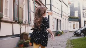 Little girl in black dress running on old road. Back view slow motion. Half-timbered houses. Happy carefree childhood. Ancient half-timbered houses. Freedom stock footage