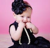 Little girl in black dress in studio Stock Image