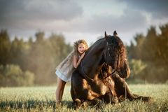 Little girl with black friesian stallion royalty free stock photo