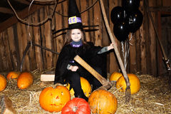 Little girl in black halloween hat and black clothing with pumpkin. Stock Photography