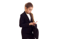 Little girl in black jacket holding diploma and smartphone Stock Photography
