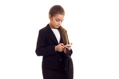 Little girl in black jacket holding diploma and smartphone Stock Photos