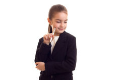 Little girl in black jacket holding pen Royalty Free Stock Photo