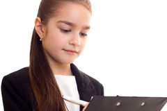 Little girl in black jacket holding pen and folder Royalty Free Stock Photo