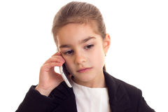 Little girl in black jacket talking on phone Royalty Free Stock Photo