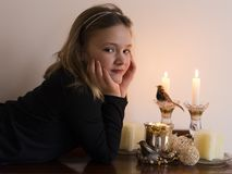 Little girl in black lying down with face in her hands next to lighted candles. Pretty little girl in black lying down with face in her hands next to lighted stock image