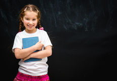Little girl  on black school board background. Cute little girl smiling on black school board background with a blue book in hand Royalty Free Stock Image