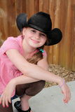 Little girl in black western hat. A little girl wearing a black western hat, with long blond ponytail , shallow depth of field Stock Photo